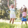 Grandmother and granddaughter at a park hula hooping and smiling — Stock Photo #4763541