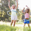 Stock Photo: Grandmother and granddaughter at park hulhooping and smiling