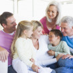 Family sitting indoors smiling — Stock Photo