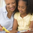 Grandmother and granddaughter reading and smiling - Stock Photo