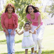 Grandmother with adult daughter and granddaughter in park - Stockfoto