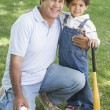 Grandfather and grandson holding baseball bat and smiling - Zdjęcie stockowe