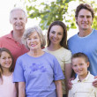 Extended family standing in park smiling — Stock Photo #4763707