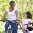 Grandmother and granddaughter on bikes outdoors smiling — Stock Photo