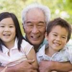 Grandfather posing with grandchildren — Stock Photo