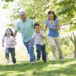 Grandparents running with grandchildren — Stock Photo