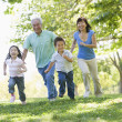 Grandparents running with grandchildren — Stock Photo #4763780