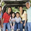 Extended family sitting in tailgate of car — Stock Photo