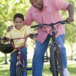 Grandfather and grandson on bikes outdoors smiling — Stock Photo