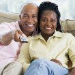 Couple relaxing in living room holding remote control and smilin — Stock Photo #4763938
