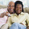 Couple relaxing in living room holding remote control and smilin — Stockfoto