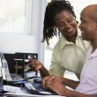 Couple in home office with credit card using computer and smilin - Stock Photo