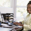 Woman in home office using computer and smiling — Stock Photo