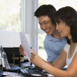Couple in home office with computer and paperwork smiling - Stockfoto