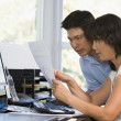 Couple in home office with computer and paperwork pointing — Stock Photo #4763999