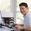 Man in home office using computer and smiling — Stock Photo #4764007