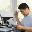 Man in home office with computer and paperwork frustrated — ストック写真