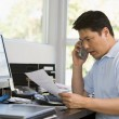 Man in home office with computer and paperwork on telephone — Stock Photo