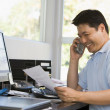 Man in home office with computer and paperwork on telephone smil — Stock Photo #4764016