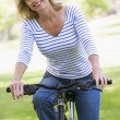 Woman on bike outdoors smiling — Stock Photo #4764036