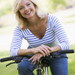 Woman on bike outdoors smiling — Stock Photo #4764041