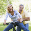 Stock Photo: Couple on bike outdoors smiling and acting scared