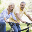 Foto Stock: Couple on bikes outdoors smiling