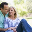 Couple relaxing outdoors in park smiling — Stock Photo
