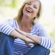 Woman sitting outdoors laughing — Stock Photo