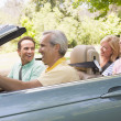Two couples in convertible car smiling - Stock Photo