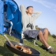 Man camping outdoors and cooking — Stock Photo