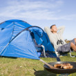 Man camping outdoors and cooking - Stock Photo