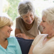Three women in living room talking and smiling — Stock Photo #4764237