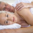 Couple lying in bed together smiling — Stock Photo #4764259