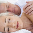 Couple lying in bed together sleeping — Stock Photo