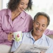 Royalty-Free Stock Photo: Couple relaxing with a newspaper smiling