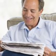 Man relaxing with a newspaper smiling — Stock Photo #4764322
