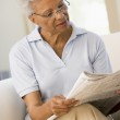 Woman relaxing with a newspaper smiling — Stock Photo