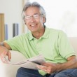 Man relaxing with a newspaper smiling — Stock Photo #4764491