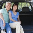 Royalty-Free Stock Photo: Couple sitting in back of van smiling