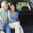 Couple sitting in back of van smiling — Stock Photo
