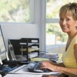 Woman in home office using computer smiling — Stock Photo