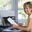 Woman in home office with computer and paperwork smiling — Stock Photo