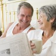Couple in bedroom with coffee and newspapers smiling — Stok Fotoğraf #4764716