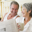 Couple in bedroom with coffee and newspapers smiling — Foto Stock #4764716