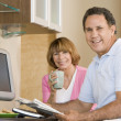Couple in kitchen with coffee and newspaper smiling — Stock Photo