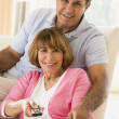 Couple in living room with remote control smiling — Foto de Stock