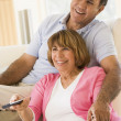Couple in living room with remote control smiling — Stock Photo #4764793