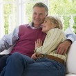 Couple in living room smiling — Stock Photo