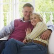 Foto Stock: Couple in living room smiling